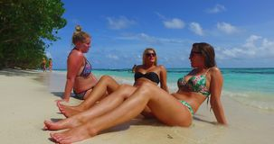 V10799 three 3 pretty young girls sunbathing on beach relaxing having fun on white sand and blue water sea royalty free stock photos