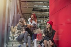 Three charming young girls talking in shopping mall royalty free stock images