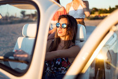 Three pretty young women driving on road trip on beautiful summe Stock Photos