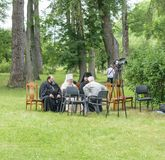 Three priests sit on chairs and talk with the man on the lawn of the museum-estate Ivan Turgenev  Stock Images