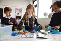 Three primary school children working together, following an instruction book and using construction blocks in a classroom, front. View, close up stock photo