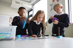 Three primary school children working together with toy construction blocks in a classroom, the girl reading instructions from a b. Ook, close up, low angle stock photo