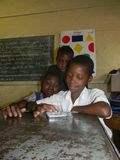 Three primary schoolkids using tablet in classroom. stock photo