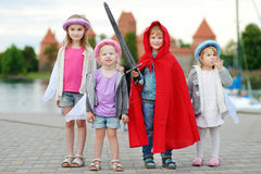 Three princesses and a knight having fun outdoors Stock Photo