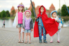 Three princesses and a knight having fun outdoors Stock Image