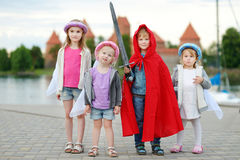 Three princesses and a knight having fun outdoors Stock Images