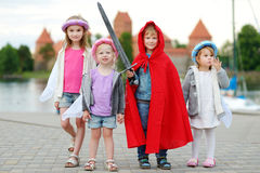 Three princesses and a knight having fun outdoors. Four kids dressed in princesses and a knight costumes having fun outdoors Royalty Free Stock Photo