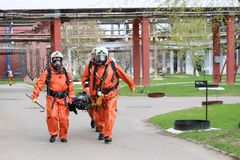 Three professional firefighter firefighters in orange protective fireproof suits, white helmets and gas masks carry the injured pe stock photos