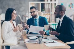 Three professional, successful, stylish, elegant employees having break time during conference, speaking, drinking tea holding mu. Gs with coffee in hands stock images