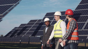 Three professionals in solar power station. Royalty Free Stock Photos