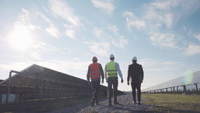Three professionals in solar power station. Stock Photos