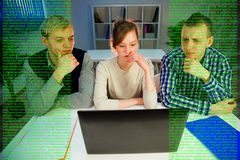Three programmers at computer Stock Images