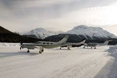 Three propeller type private jet and planes in the snow covered airport in the alps switzerland in winter.  stock images