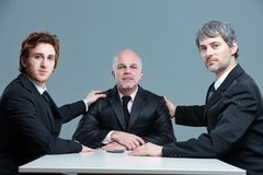 Three proud business partners posing together. With two young men flanking an older man, holding him by the shoulders in a sign of unity while seated at a table royalty free stock images