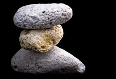Three pumice stones on black Stock Photos