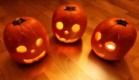 Three pumpkin faces on the wooden floor Royalty Free Stock Photo