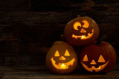 Three pumpkin Jack-O-Lantern with happy faces. Carved Halloween pumpkins with burning candles inside. Halloween festive decorations royalty free stock photo