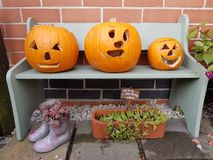 Three pumpkins carved by children for Halloween, All Hallows Eve Royalty Free Stock Images