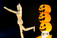 Three pumpkins scare wooden puppet away Royalty Free Stock Images