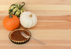 Three pumpkins with small pumpkin pie and fork Royalty Free Stock Photo