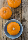 Three pumpkins on wooden background Royalty Free Stock Photos