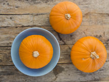 Three pumpkins on wooden background Stock Images