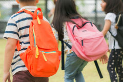 Three pupils of primary school go hand in hand. Boy and girl with school bags behind the back. Beginning of school lessons. Warm day of fall. Back to school royalty free stock photo