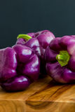 Three purple bell peppers. Purple bell peppers, Sweet Pepper Tequila, Capsicum annum, on a wooden board against a dark blue background with copy space. Selective royalty free stock image