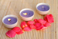 Three purple candles. With rose petals on bamboo Royalty Free Stock Image