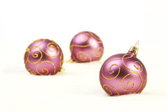 Three purple christmas balls with gold lines on white background Stock Photography