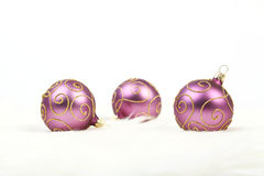 Three purple christmas balls with gold lines on white background royalty free stock photography