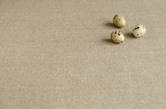 Three quail eggs on a linen tablecloth Stock Photo