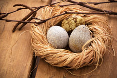 Three quail eggs in a nest. On wooden background Royalty Free Stock Photography