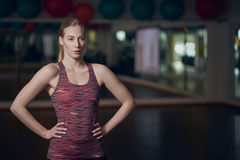 Three quarter body portrait of athletic young woman. Posing in gym with hands on hips Stock Photo