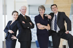 Three quarter length vew of four businesspeople. Portrait of four businesspeople smiling in an office corridor after successful meeting over contracts Royalty Free Stock Photography