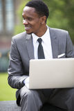 Three-quarter portrait of African American Businessman working on a laptop outdoors Stock Photos