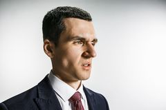 Three-quarter portrait of a businessman with disgust face. Confident professional with piercing look in the foreground. Of the camera. Diplomat on the white Stock Images