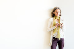 Three quarter view of middle aged woman using smart phone. Three quarter length view of natural looking middle aged woman with grey hair and green scarf using Royalty Free Stock Images