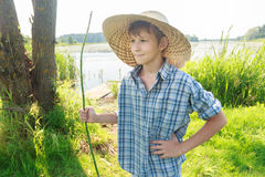 Three-quarter view portrait of relaxing angler teenage boy wearing plaid shirt and straw hat Stock Photos