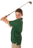 Young boy swinging a golf club. A three-quarter view of a young boy swinging a golf club over his shoulder isolated on a white background Royalty Free Stock Photo