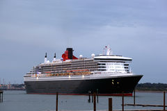 Three Queens Event 3. SOUTHAMPTON, UK - 5 JUNE: Cunard ship Queen Mary 2 sails in at dawn to meet Queen Elizabeth & Queen Victoria in the port of Southampton for Royalty Free Stock Image