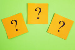 Three Question Marks Orange on Green Background Stock Image