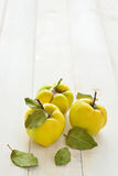 Three quinces on background board Royalty Free Stock Photo