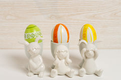 Three rabbits in front of egg cups with hand painted easter eggs Stock Images