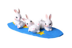 Three rabbits and surfboard. Stock Images