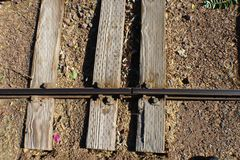 Three rails road ties with one rail weathered with bolts Royalty Free Stock Images