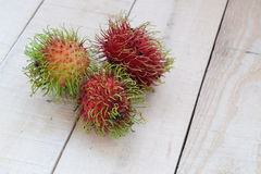 Three Rambutans on wooden panels Stock Images