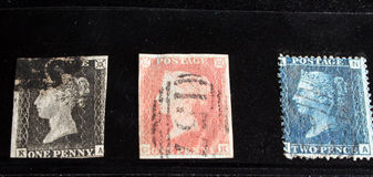 Three Rare British Stamps. The worlds first three postage stamps. 1840 Penny Black. 1841 Penny Red. Two Penny Blue royalty free stock photos