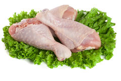 Three raw chicken drumsticks with lettuce leaf isolated on white background Royalty Free Stock Photography