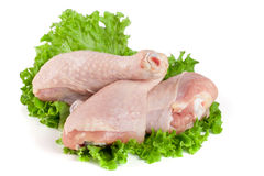 Three raw chicken drumsticks with lettuce leaf isolated on white background Stock Photos